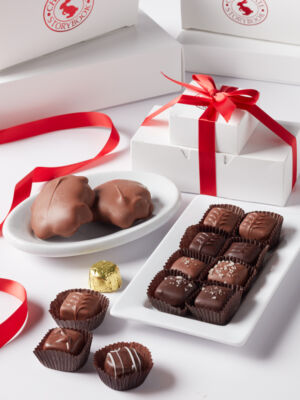 Two tier white box perfect gift set filled with turtles, caramels and assorted chocolates and tied with a red satin bow.