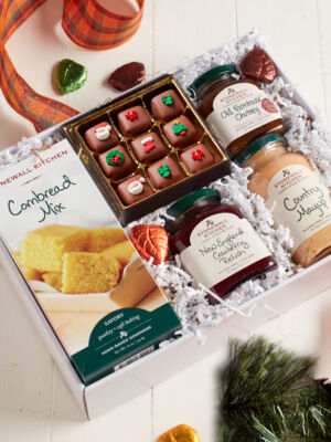 White box filled with a holiday feast of chocolate caramels, cornbread and gourmet jams and sauce.