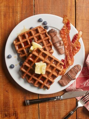 chocolate covered bacon and waffles on plate