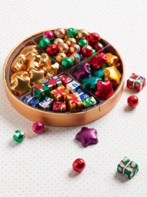 round tray filled with foil chocolate stars, presents and balls in assorted colors
