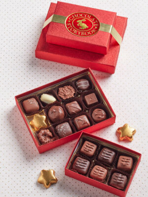 two red boxes of assorted chocolates, creams and caramels tied with a gold bow with sweet layers